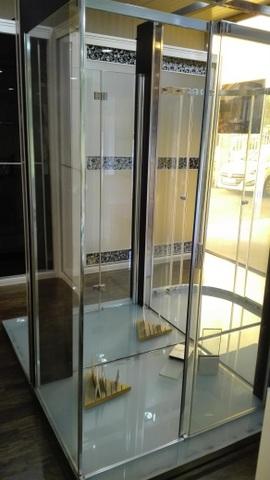 Cabina de ducha formada por frente con puerta corredera y fijo lateral de vidrio transparente templado de 8mm