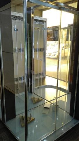 Cabina de ducha formada por frente con puerta corredera y fijo lateral de vidrio transparente templado de 8 mm